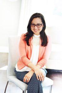 Femme asiatique qui sourit les mains croisées